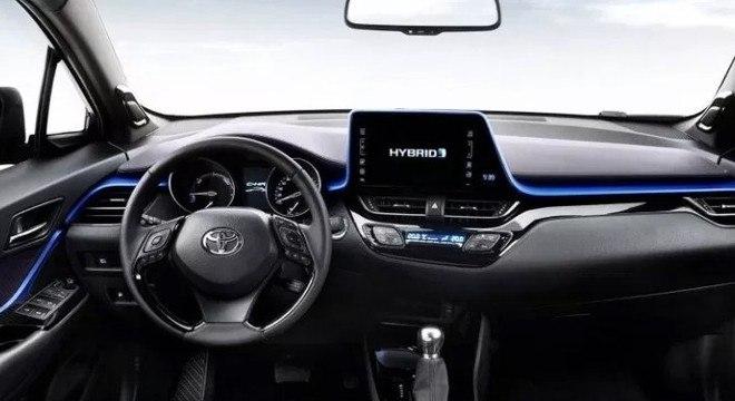 Interior do C-HR híbrido: contorno azulado sobre o painel e identidade alinhada ao design atual