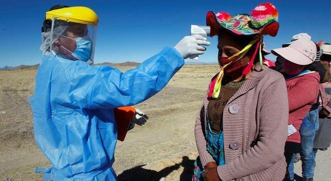 Trabalhador da saúde verifica a temperatura de mulher indígena no Peru
