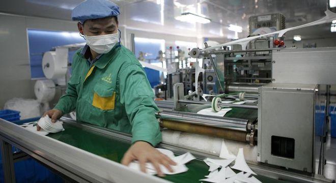 Homem trabalha em fábrica de máscaras na China
