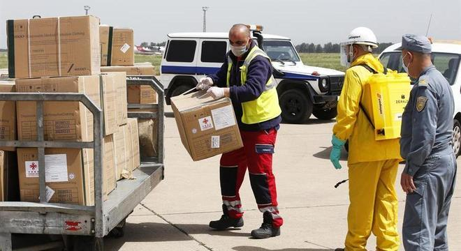 Trabalhadores descarregam suprimentos médicos em aeroporto da Argélia