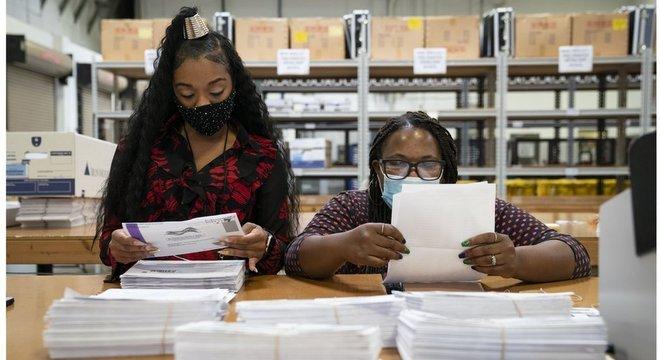 Trabalhando em duplas bipartidárias, funcionárias processam votos pelo correio no Estado de Maryland, o primeiro a começar a processar os votos remotos no país
