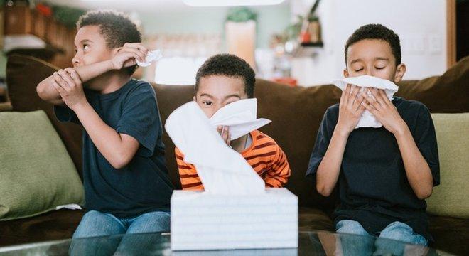 Três garotos em casa usam lenços durante tosse e espirro.
