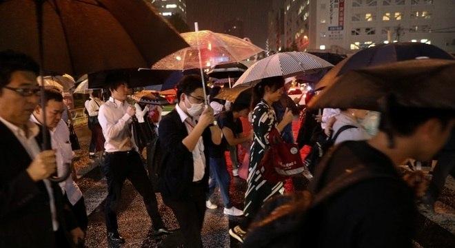 Moradores de Tóquio se protegem da chuva que já chegou ao país
