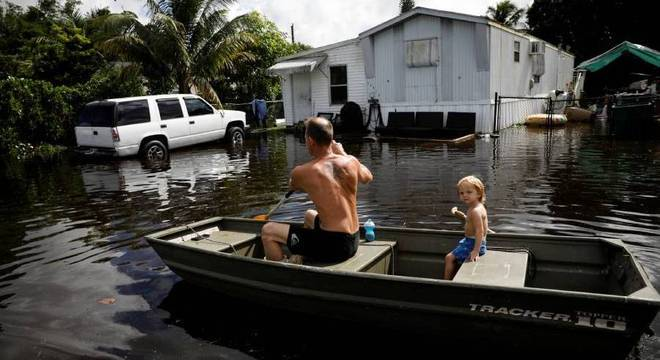 Um homem rema um barco na enchente causada pela tempestade Eta em Davie