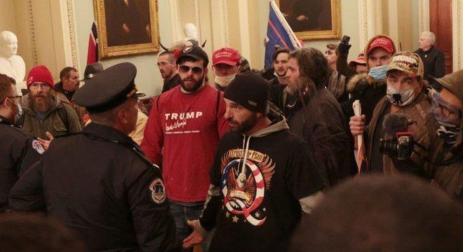 Um manifestante vestindo uma camisa com o slogan do QAnon 'Confie no plano' fala com a polícia dentro do prédio do Capitólio dos EUA na quarta-feira