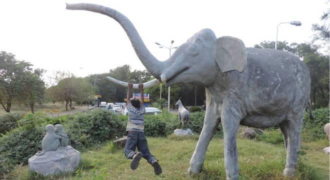 Menino se balança em uma estátua de elefante na avenida fora do zoológico de Islamabad