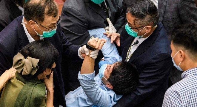 Um parlamentar é detido por guardas no Conselho Legislativo de Hong Kong durante um conflito sobre um projeto de lei sobre o hino nacional