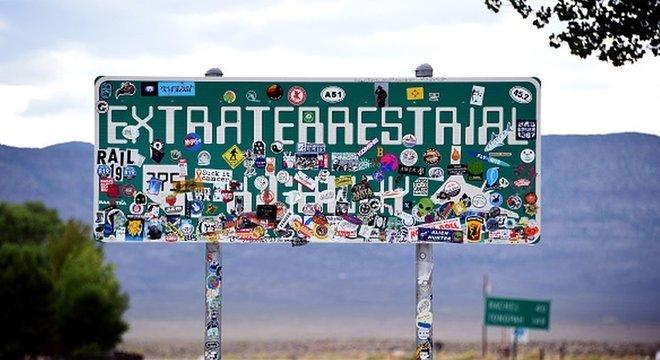 Placa de trânsito da 'Estrada para Extraterrestres', coberta com adesivos, na Rota 375