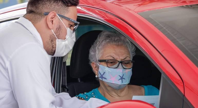 Profissionais da saúde aplicam a dose da vacina Fiocruz/AstraZeneca, contra a Covid-19, em idosos no drive-thru do shopping Aricanduva, em São Paulo,