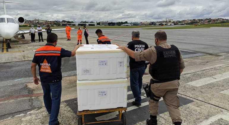 Policiais militares e civis fazem transporte das vacinas para o interior do Estado