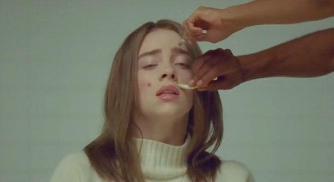 Billie Eilish aparece com o rosto queimado por cigarros em seu novo clipe,