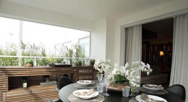 Varanda gourmet com mesa redonda preta e cadeiras da mesma cor Projeto de Carlos Rossi