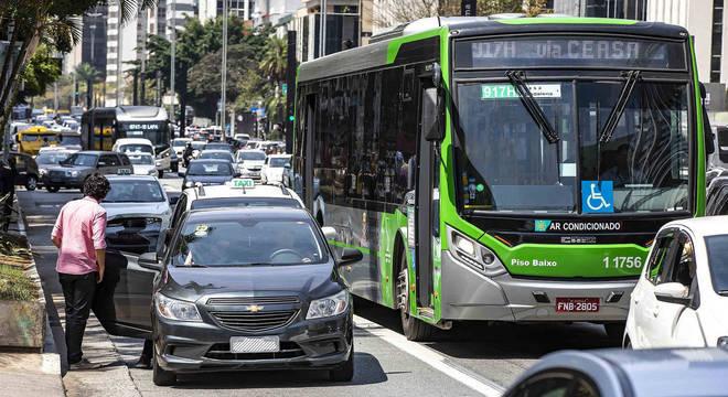 Veículo de app pega passageiro na faixa da Paulista, enquanto ônibus desvia