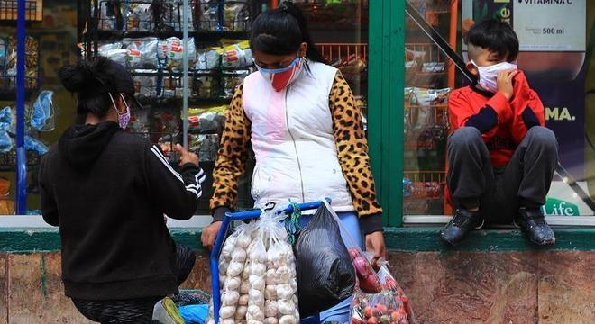 Vendedora informal usa máscara para trabalhar nas ruas de Quito
