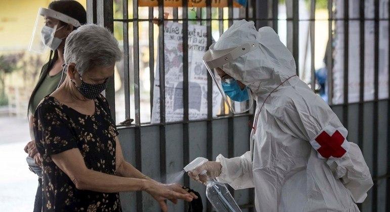 Profissional de saúde higieniza mão de idosa na Venezuela