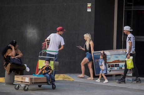 Famílias carregam compras da Black Friday em Caracas