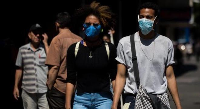 Pedestres se previnem usando máscaras em Caracas