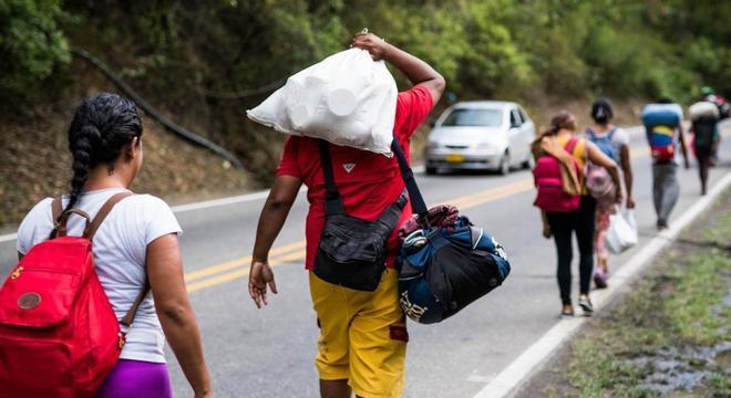 Migrantes cruzam a fronteira da Venezuela com a Colômbia, a pé, carregando seus pertences