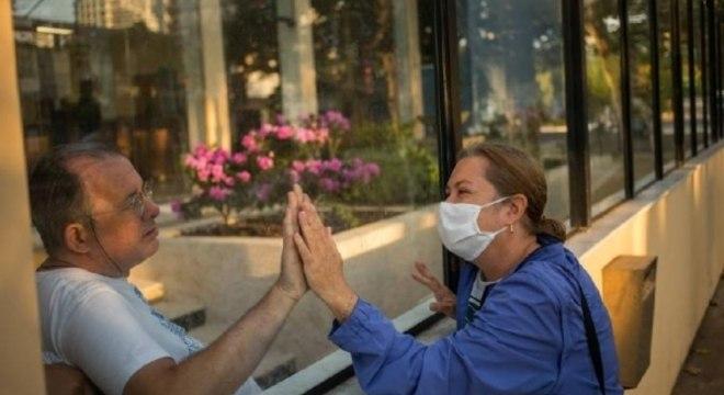 Liliane Moretti visita o marido Fabio Moretti por um muro de vidro do hospital