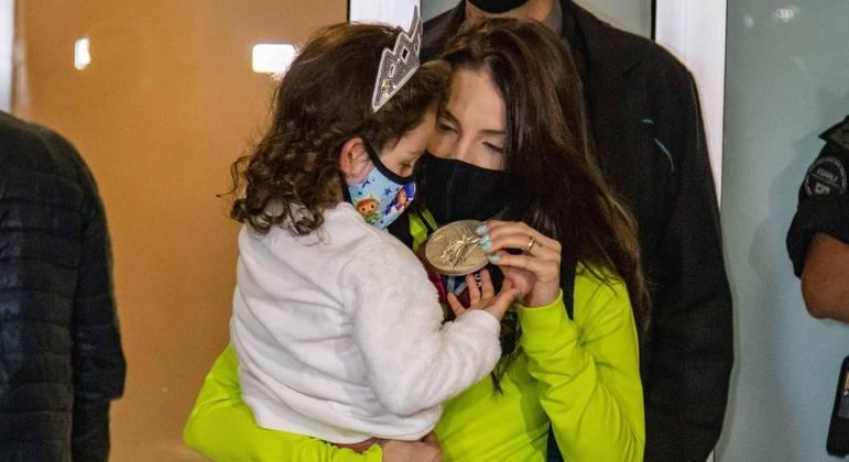 A jogadora Camila Brait mostra a medalha para a sua filha na chegada ao Brasil