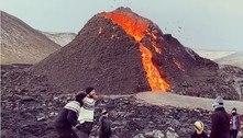 Grupo de amigos joga vôlei em frente a vulcão em erupção