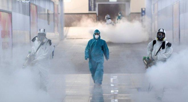 Voluntários desinfectam estação de trem na província de Hunan, na China
