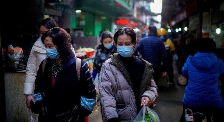 Pessoas caminhando por um mercado de rua na cidade