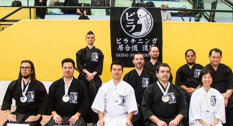 o tricampeão Yuji Yamauchi (ao centro, de branco) e sua equipe em São Paulo