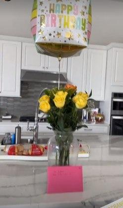 Ele enviou para a aniversariante um buquet de rosas amarelas presas a um balão colorido