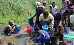 Mulheres e crianças pegam água suja no Zimbábue. A cidade de Luveve registrou ao menos 700 casos confirmados de diarreia, 240 deles em um único dia, em 14 de outubro, de acordo com as autoridades locais. Este é um segundo surto em quatro meses, com 100 casos envolvendo crianças. Em junho, um surto de diarreia matou 13 pessoas e infectou quase 2.000 pessoas